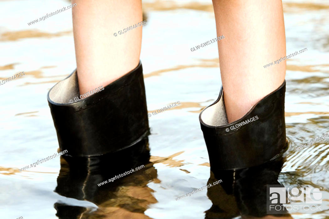 Stock Photo: Low section view of a person wearing rubber boots.