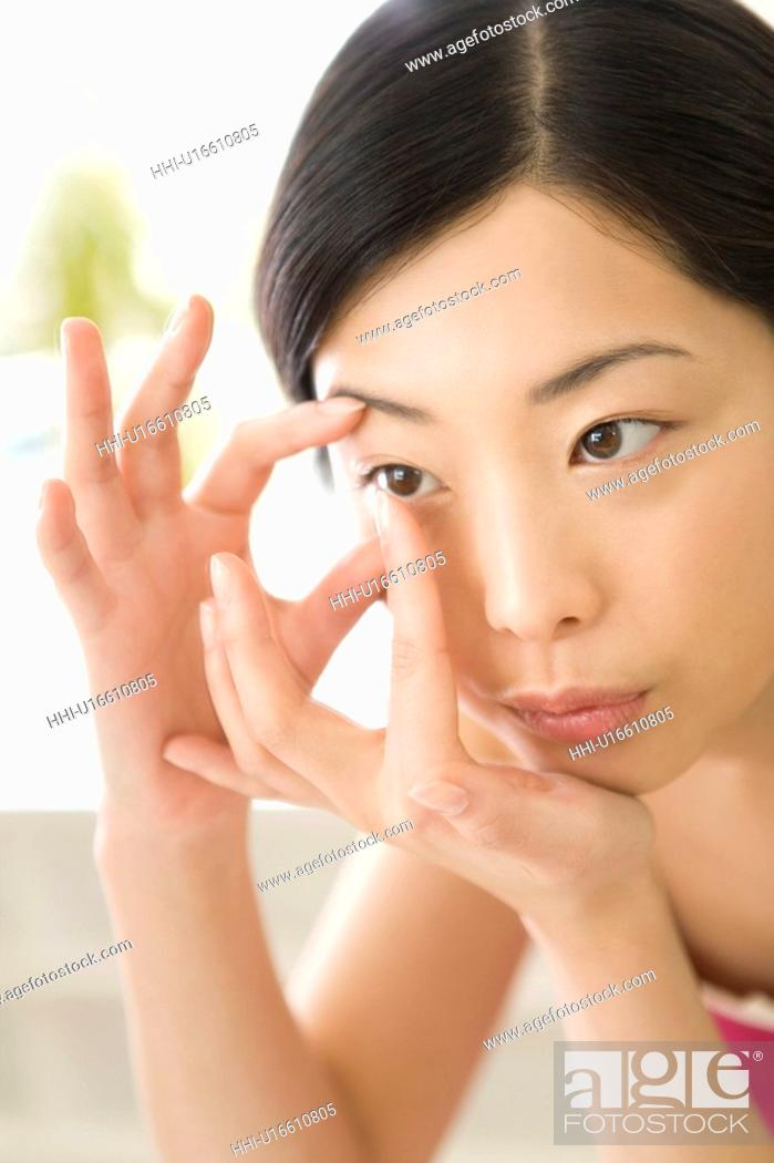 Stock Photo: Young Woman inserting contact lens, Close Up, Front View.