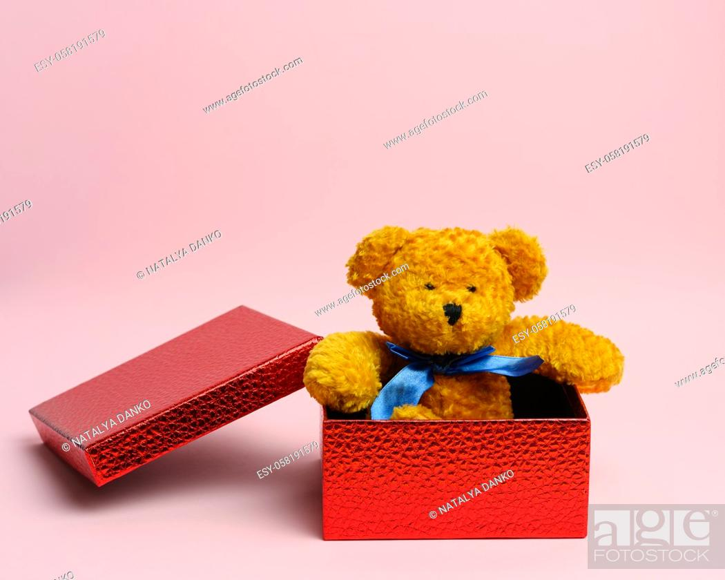 Stock Photo: cute teddy brown bear sitting in a red gift box on a pink background.