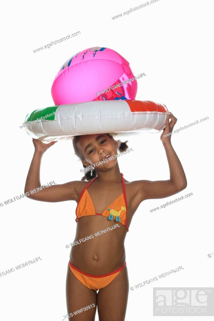 Stock Photo: African girl 6-7 holding floating tire and beach ball, smiling, portrait.