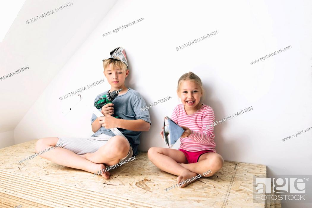 Stock Photo: Happy brother and sister in a home to be renovated.