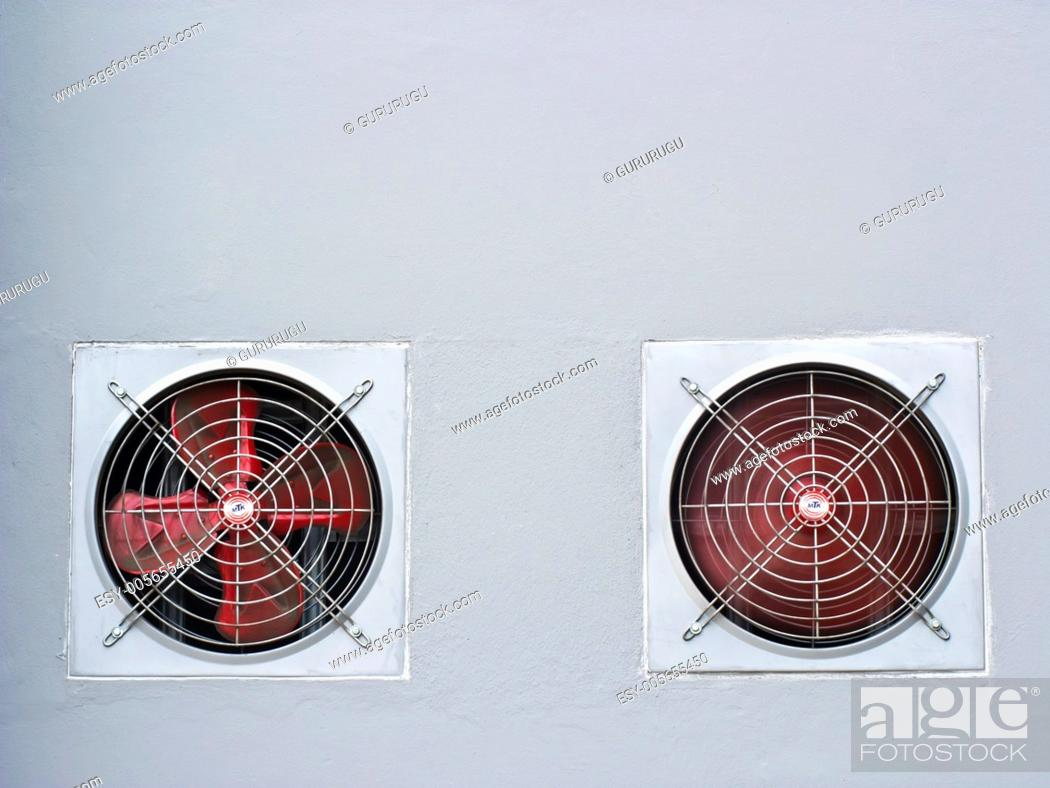 Stock Photo: A pair of red industrial ventilated fan on grey wall as background.