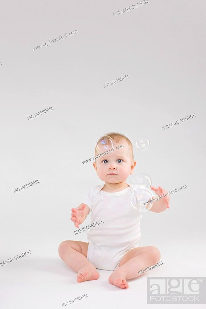 Stock Photo: Baby looking at bubbles.