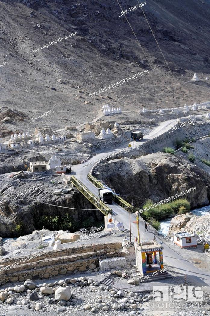 Stock Photo: Bridge in the Hundar oasis over a tributary of the Shyok River with military convoy, guard post, prayer wheel, Chorten and Mani (prayer inscribed) wall.