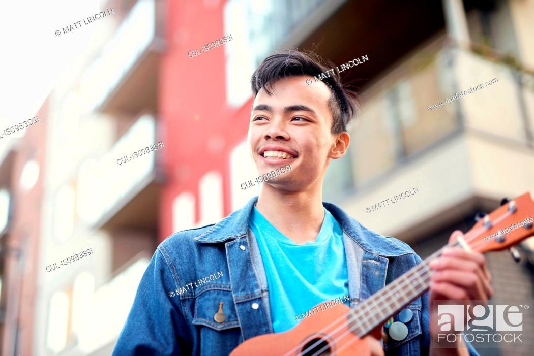 Imagen: Young man on street playing ukulele.