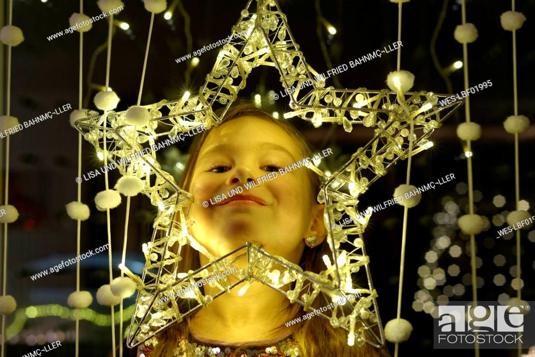 Stock Photo: Portrait of smiling little girl looking through Christmas star.