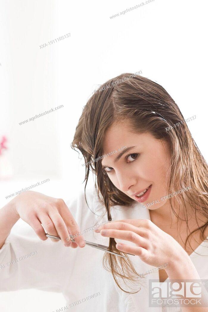 Imagen: Woman cutting hair endings.