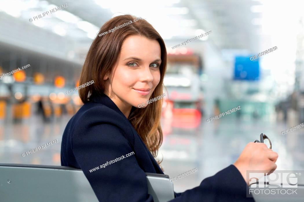 Stock Photo: Portrait of businesswoman looking over her shoulder in airport departure lounge.