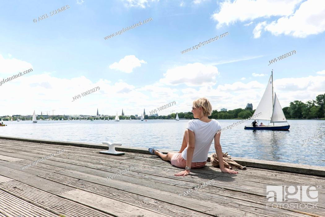 Stock Photo: Woman enjoying view of alster lake at Winterhude, Hanseatic City of Hamburg, Germany.
