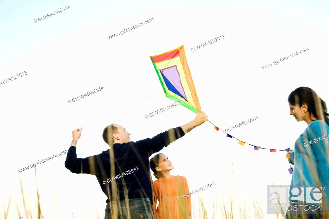 Stock Photo: Rear view of a mid adult man with his family flying a kite.