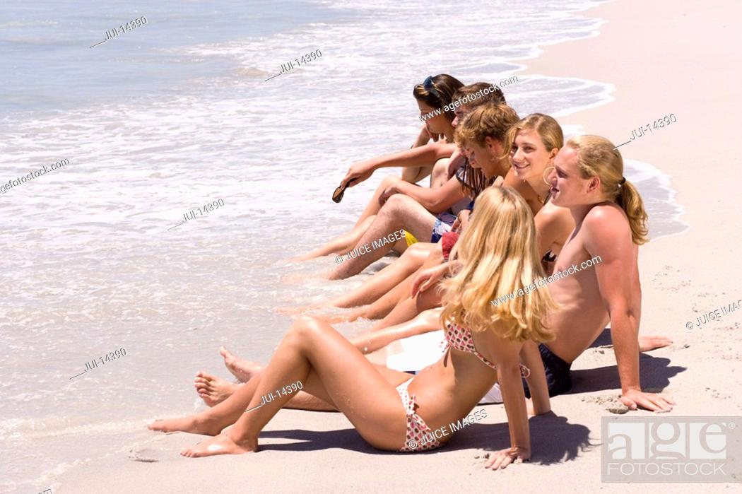 Stock Photo: Group of teenagers 15-17 sitting in line on beach, side view.