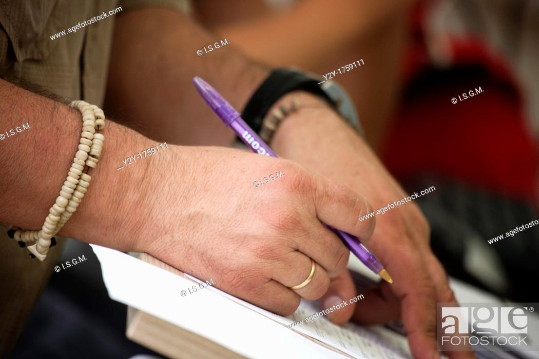 Stock Photo: Man hand with pen and bracelet.