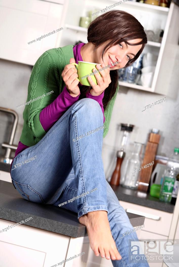 Stock Photo: woman in kitchen drinking hot beverage.