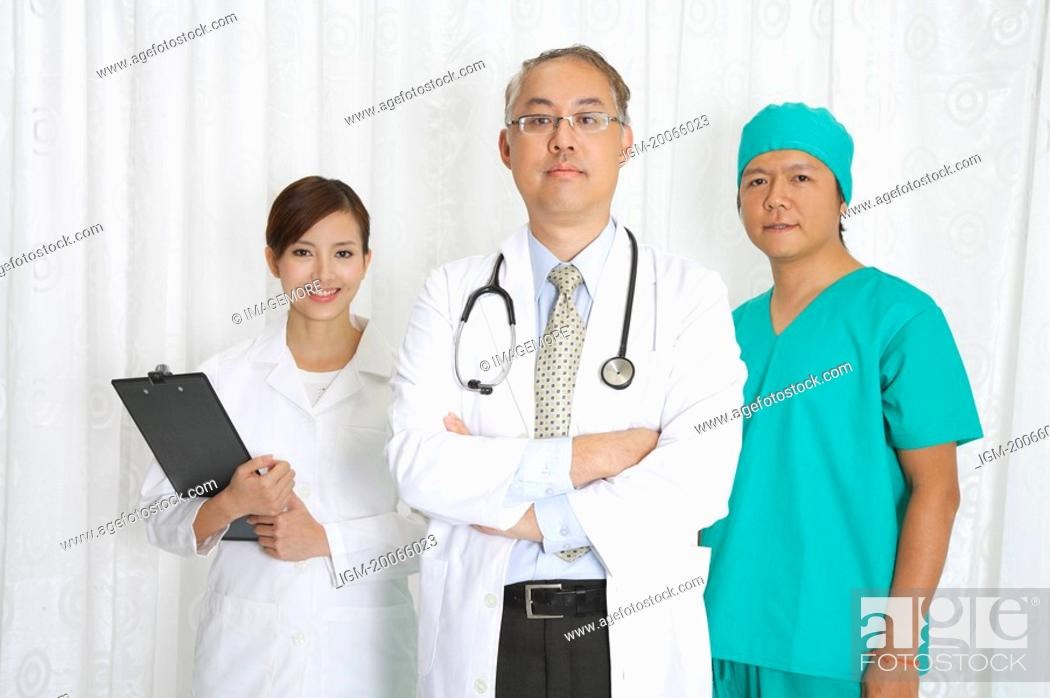 Stock Photo: Doctor, female doctor and surgeon standing together and looking at the camera.