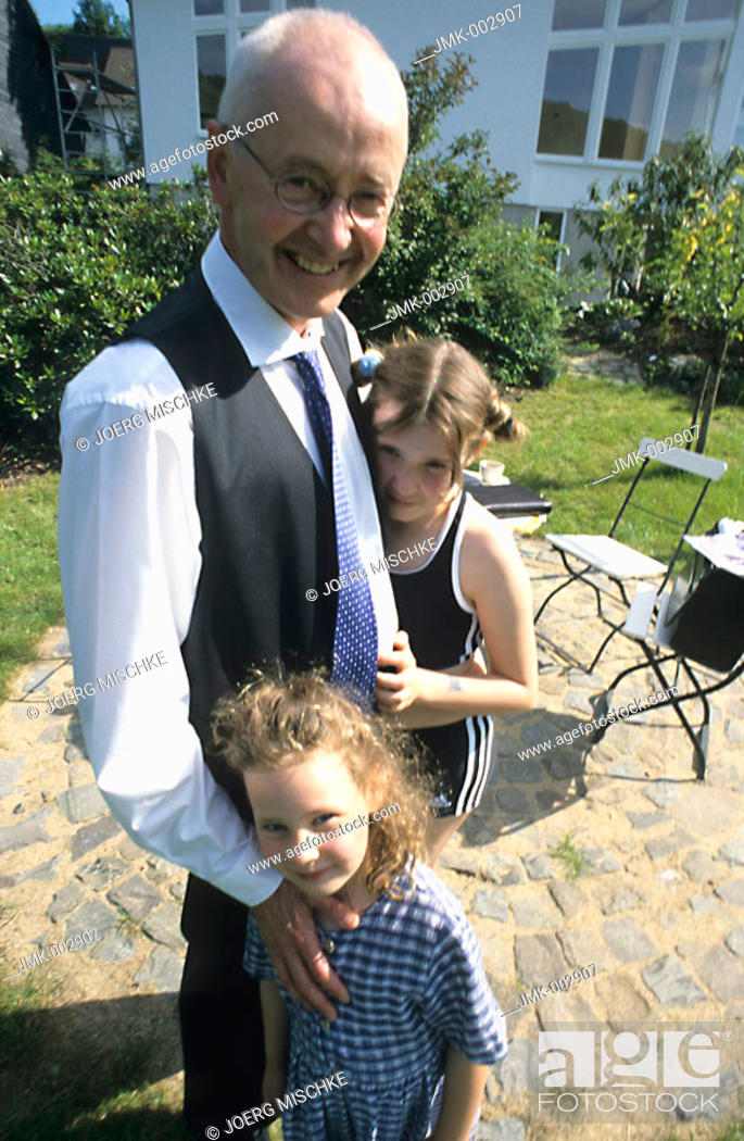 Stock Photo: A senior, businessman, father, grandfather, 45-50 50-55 55-60 years old, and two girls, 1-5 5-10 years old, in a summerly garden.