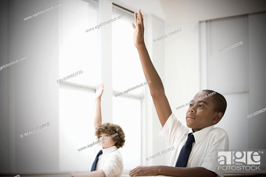 Stock Photo: School students with hands raised.