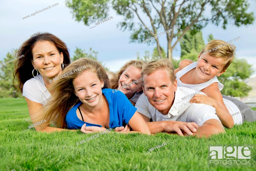 Stock Photo: Portrait of a family of five in a dog pile near a lake.