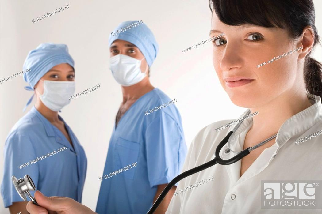 Stock Photo: Portrait of a female doctor with two surgeons in the background.