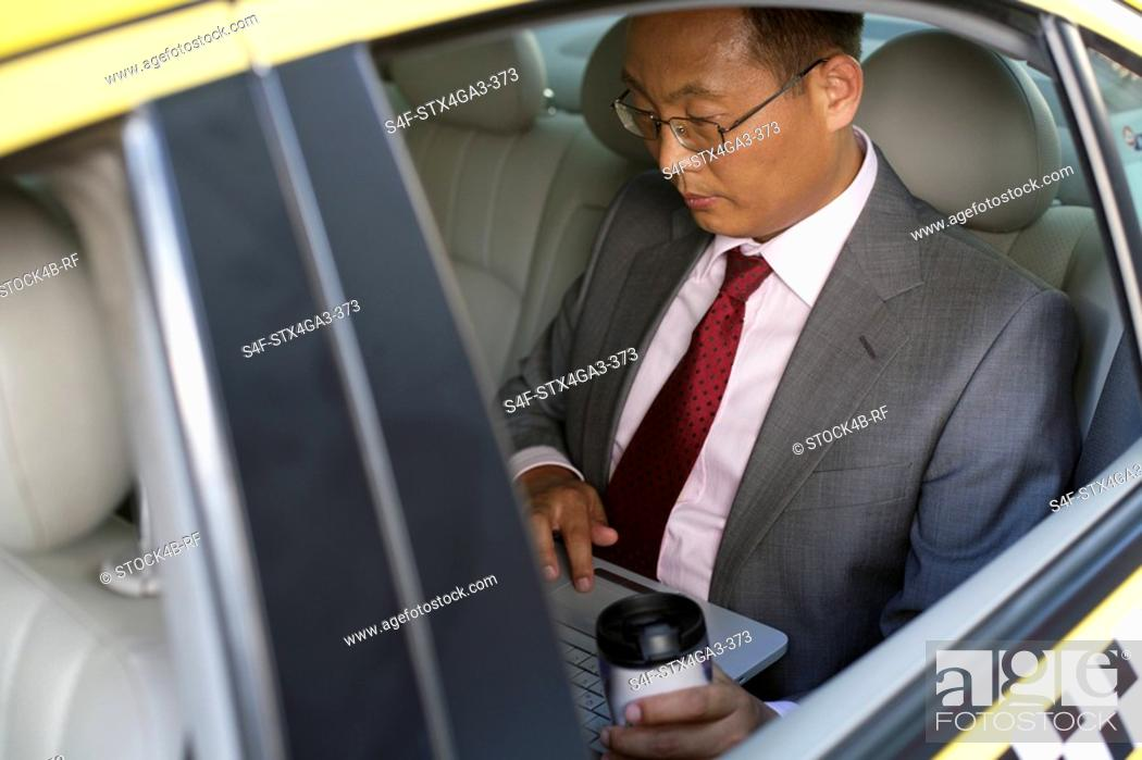 Stock Photo: Businessman using laptop in a car.