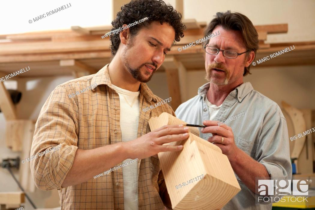 Stock Photo: Co-workers woodworking in workshop.