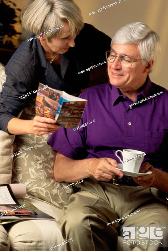 Stock Photo: Senior woman showing an elderly man a book.