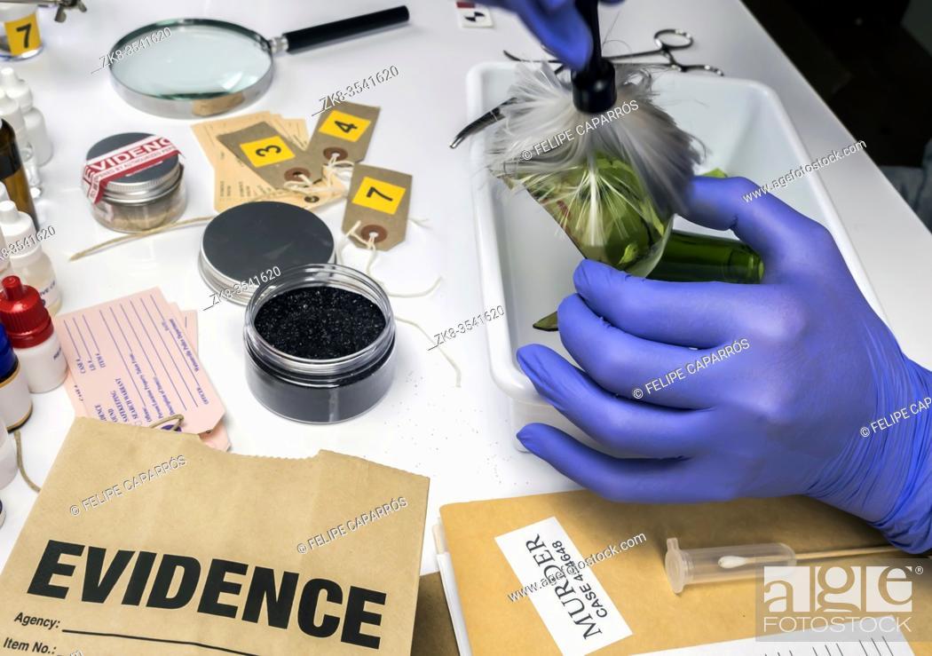 Stock Photo: Expert Police get fingerprints from a broken glass bottle in Criminalistic Lab, conceptual image.