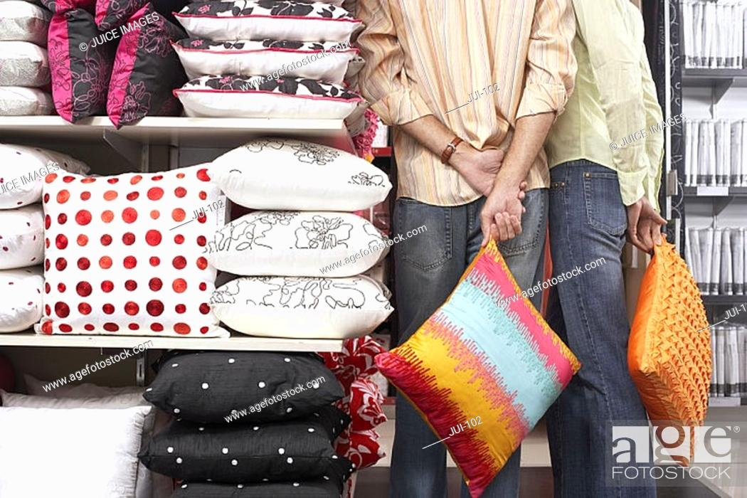 Stock Photo: Couple standing beside shelf in shop, carrying orange cushions, hands behind back, rear view.