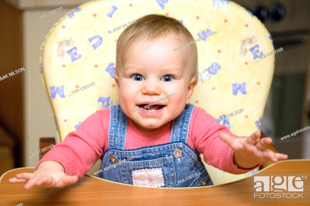 Stock Photo: Happy Smiling Eight Month Old Infant Girl in High Chair.