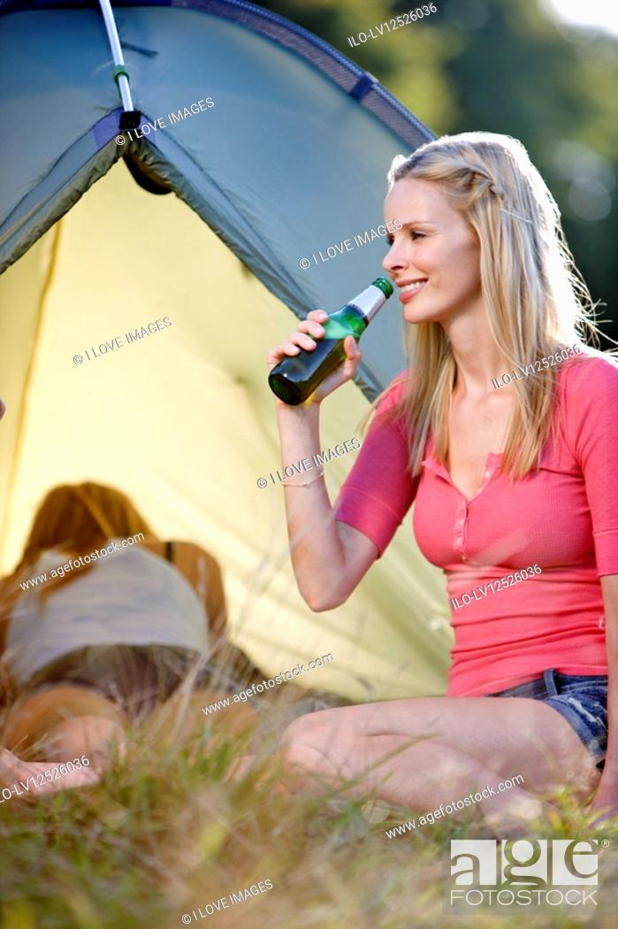 Stock Photo: Two young women camping, one drinking a bottle of beer.