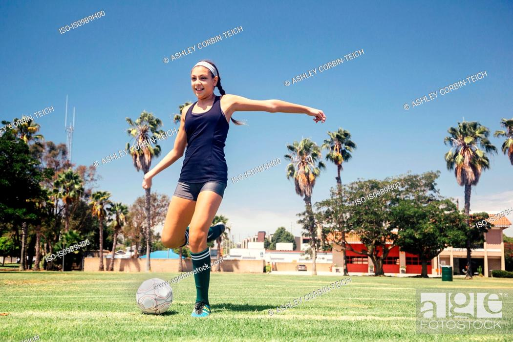 Imagen: Schoolgirl soccer player kicking ball on school sports field.
