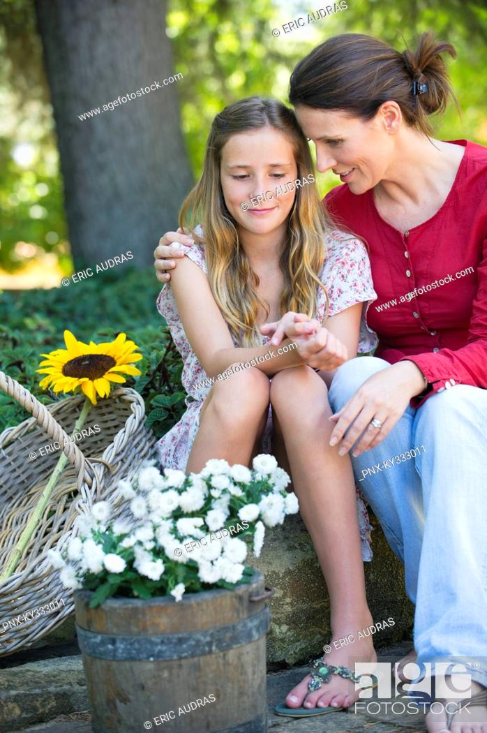 Stock Photo: Little girl and mother sitting outdoors with flowers in the basket.