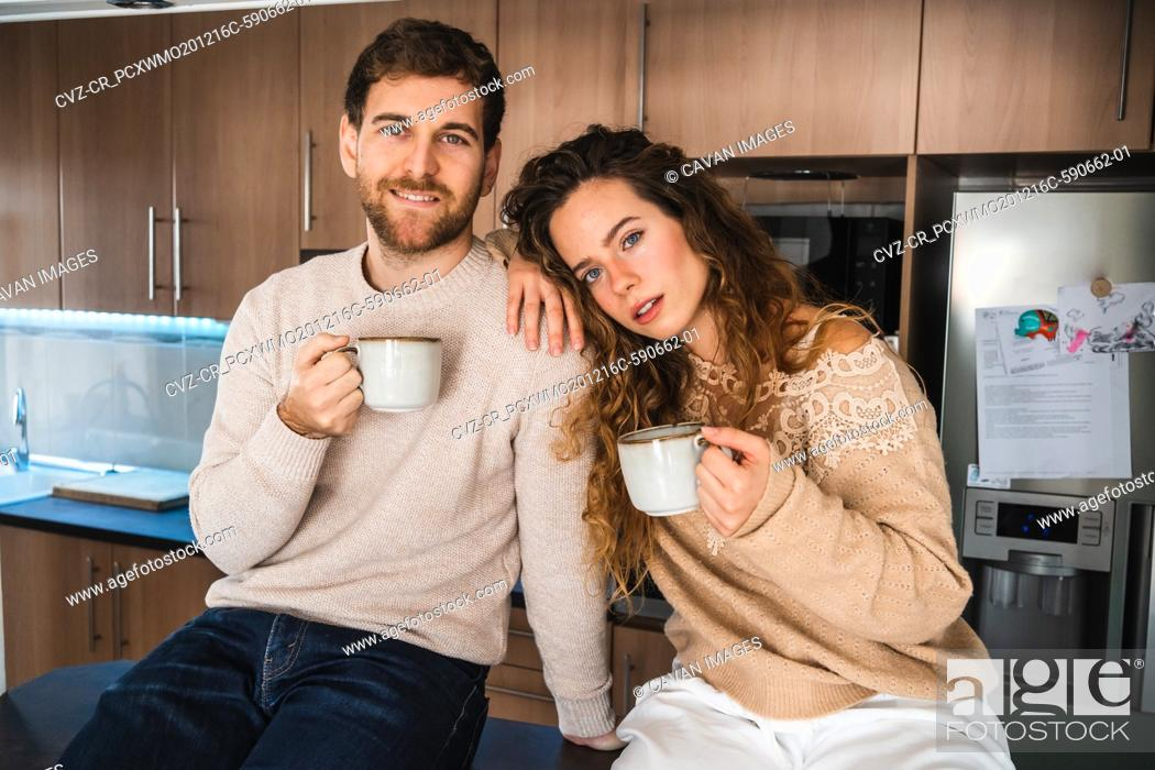 Stock Photo: Young couple with hot beverage in kitchen at home looking at camera.