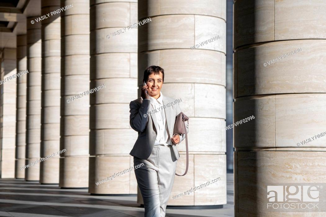 Stock Photo: Businesswoman talking on mobile phone while walking against pillar.