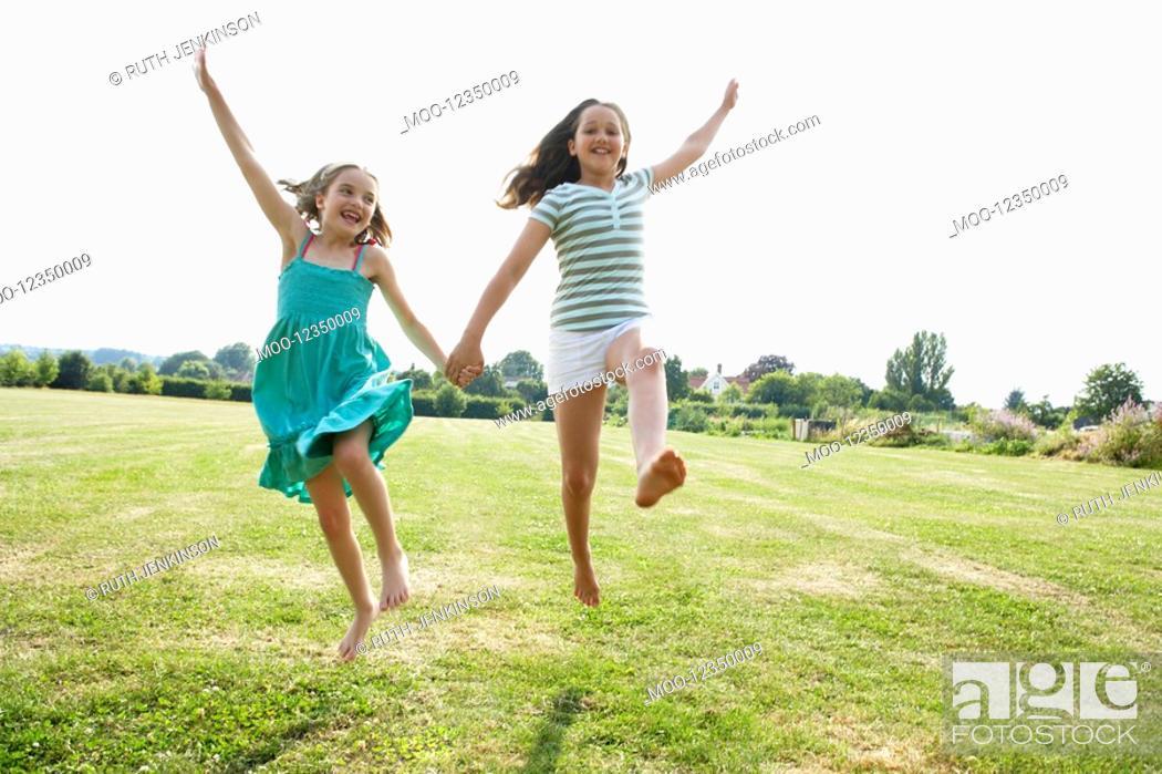 Stock Photo: Girls Running and jumping Hand in Hand through field.