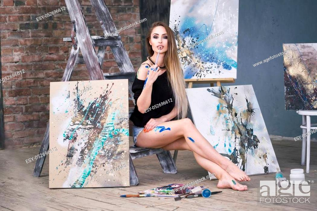 Imagen: Young female artist painting abstract picture in studio, beautiful sexy woman portrait.