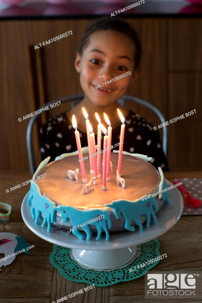Girl Preparing To Blow Out Candles On Birthday Cake Stock Photo