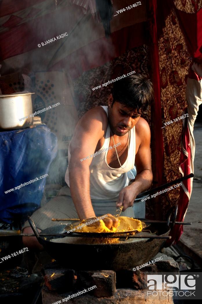 Stock Photo: Man cooking in the street, Pushkar, Rajasthan, India.