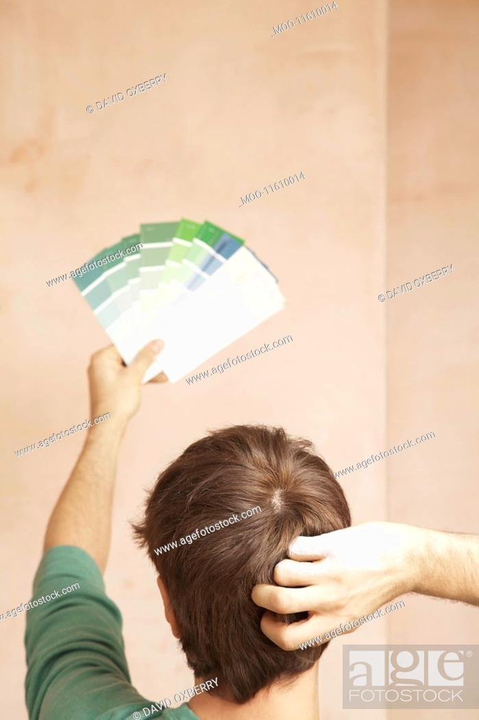 Stock Photo: Man looking at paint colour swatches in unrenovated room back view.