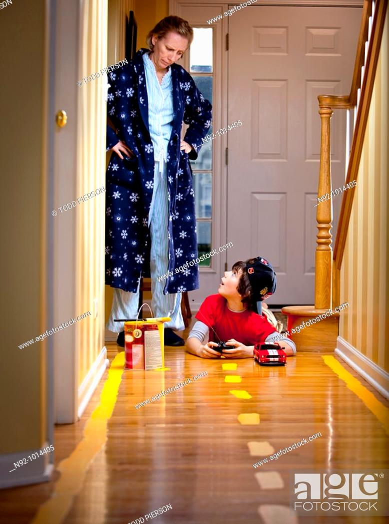 Stock Photo: Boy caught after painting stripes on floor to race car in hallway.