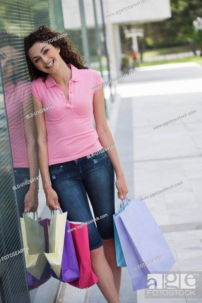 Stock Photo: Woman posing with shopping bags in front of store window.