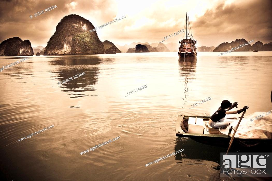 Stock Photo: A young girl rows her boat on the waters of HALONG BAY, Vietnam.