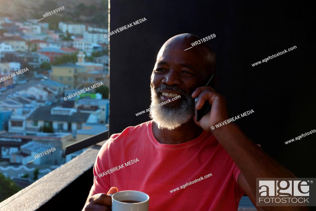 Stock Photo: Senior man having coffee while talking on mobile phone.