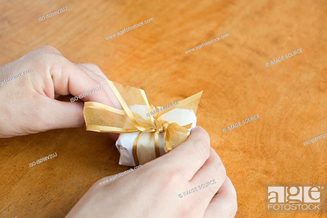 Stock Photo: Person wrapping small gift.