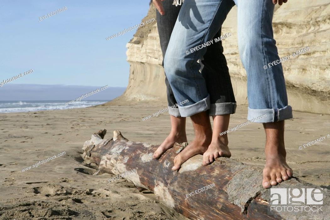 Stock Photo: Cropped view of couple balancing on log at beach.
