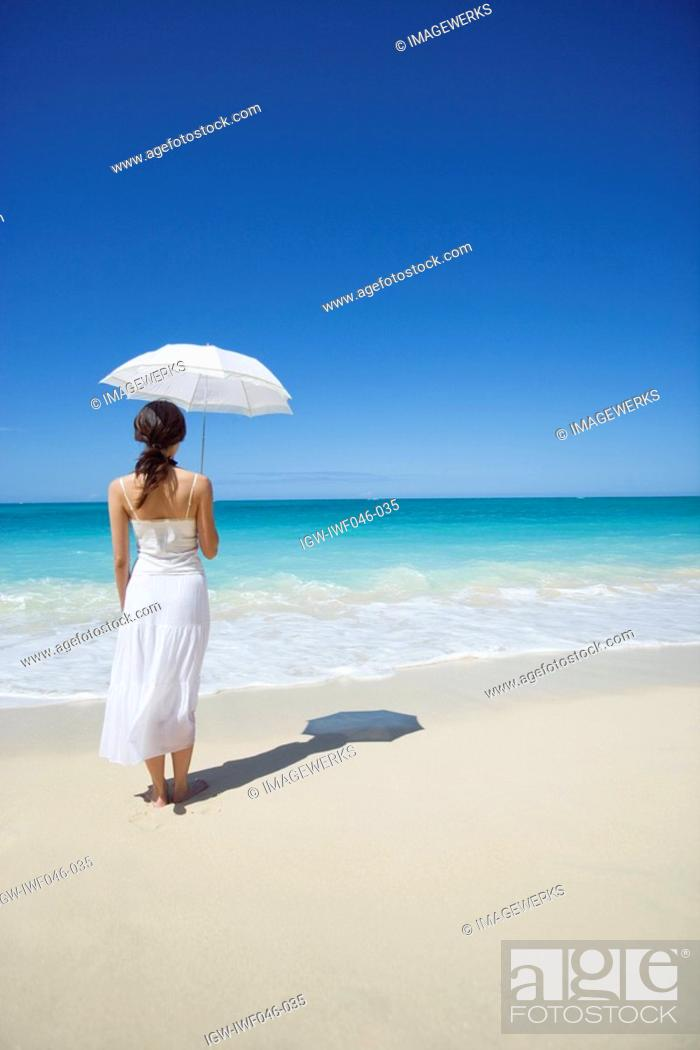 Stock Photo: Rear view of a woman holding umbrella.