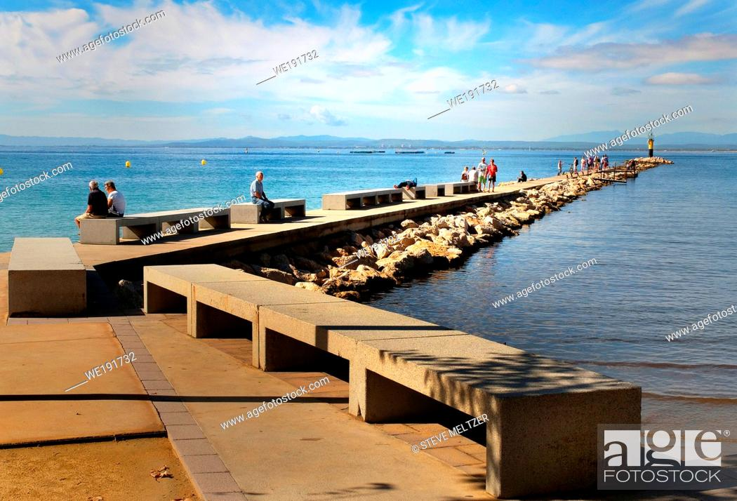 Stock Photo: The long walkway over the breakwater is a popular tourist attraction that extends from the beach at Roses, Spain.