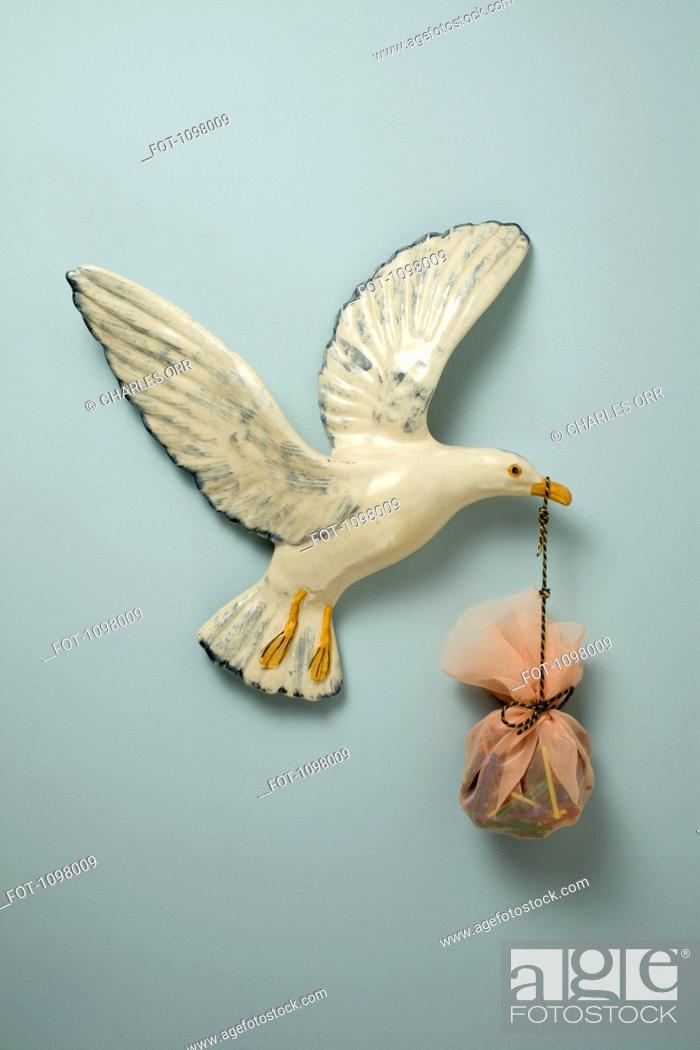 Stock Photo: A plastic bird carrying a sack in its beak, hanging on wall.