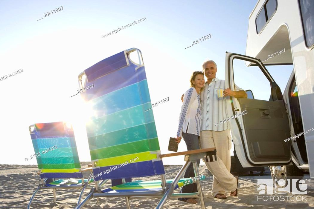 Stock Photo: Mature couple arm in arm by motor home on beach, portable chairs in foreground, low angle view sun flare.