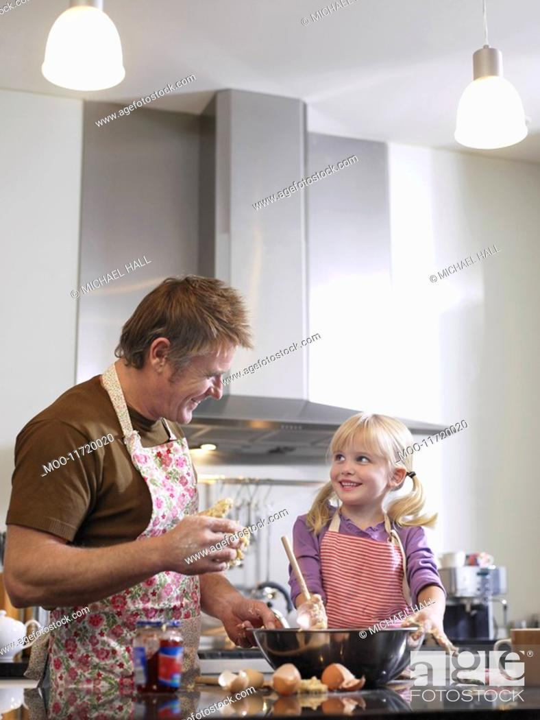 Stock Photo: Girl 3-4 and father baking in kitchen.