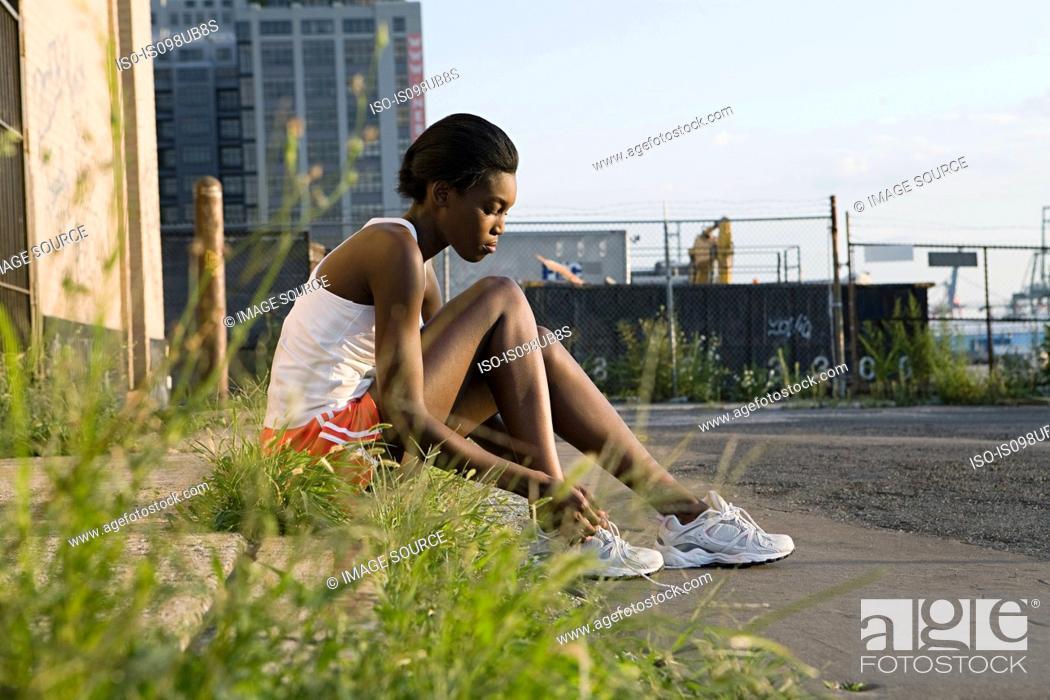 Stock Photo: Runner sitting on sidewalk.